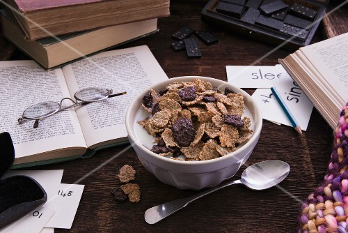 Cornflakes with milk surrounded by books