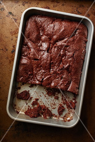 Chocolate cake, sliced, in a baking tin