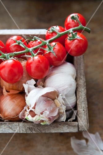 Fresh tomatoes, onions and garlic in wooden box