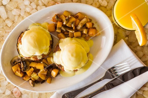 Eggs Benedict with fried potatoes and mushrooms