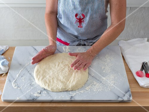 Dough being patted flat on a marble slab