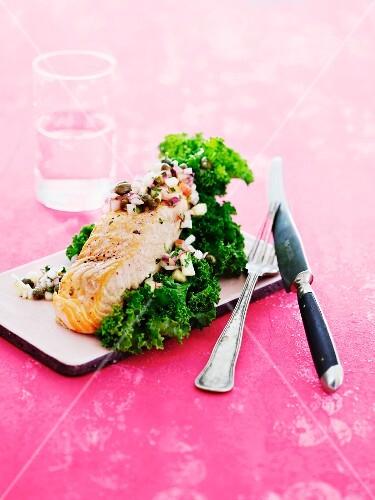 Fried salmon steak with salsa on green kale