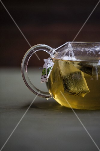 Green tea with tea bags in a glass teapot