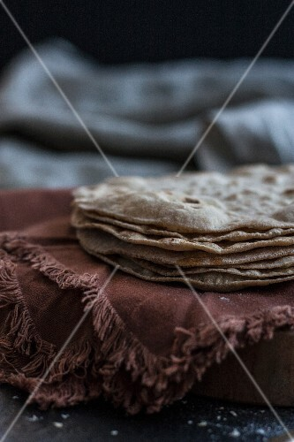 A stack of unleavened bread on a brown cloth