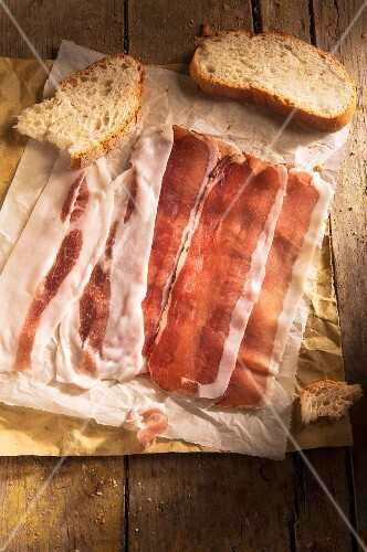 Slices of ham and bread on a piece of paper