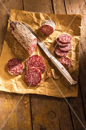 Salami, sliced, on a piece of paper with a knife