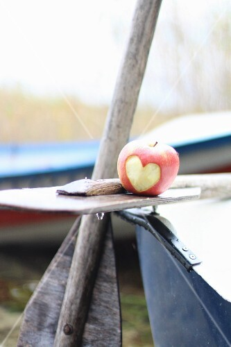 An apple with a heart carved into it on a boat