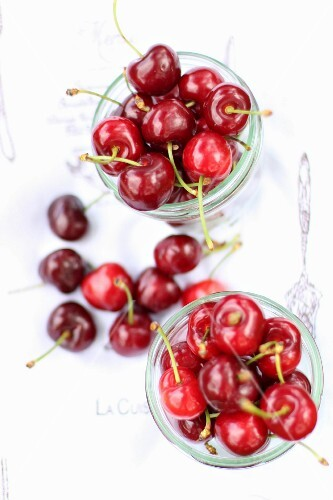 Fresh cherries in glasses and next to them