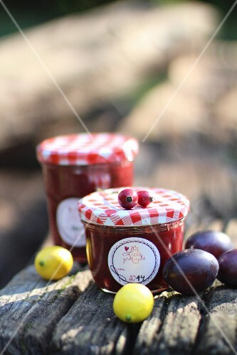 Jars of plum jam on a wooden board
