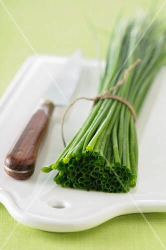 A bundle of chives and a knife on a chopping board