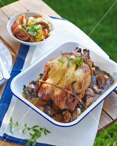 Barbecue chicken on a bed of shallots with a tomato salad