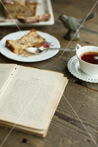 Pear cake with candied ginger and chocolate, a cup of tea and a book
