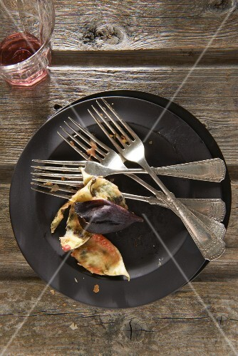 A black plate with dirty forks and fig skins, next to an empty glass of red wine