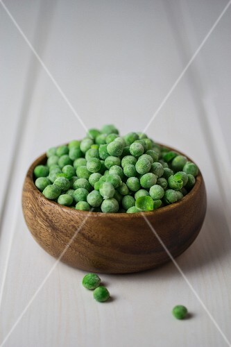 Frozen peas in a wooden bowl