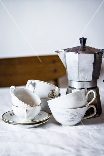 Old-fashioned coffee cups and an espresso machine