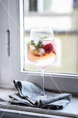 A raspberry cocktail on a window sill in a kitchen