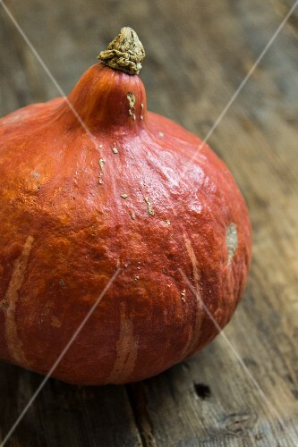 An orange pumpkin on a wooden surface