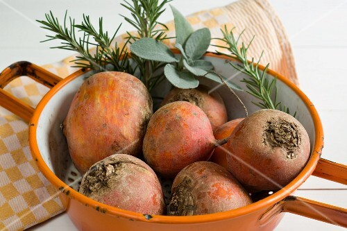 Golden beets in a colander with rosemary and sage