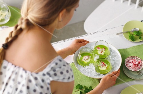 A woman serving cold pea soup with wasabi creme fraiche and radishes