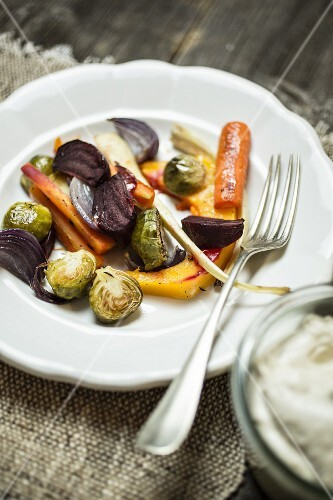 Oven-roasted vegetables on a plate with a fork