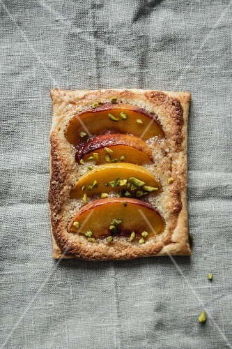 A peach tartlet with chopped pistachios