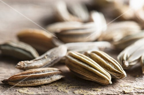 Fennel seeds on a wooden surface (close-up)
