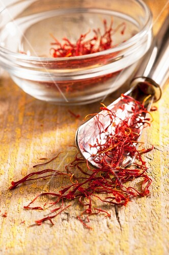 Saffron threads on a spoon and in a glass bowl