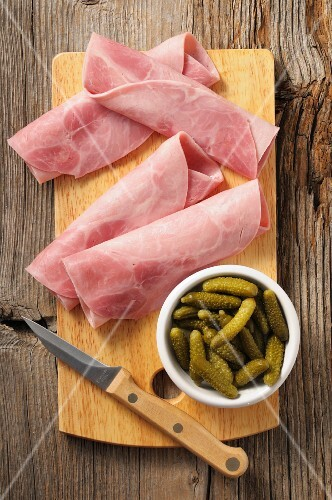 Rolled ham and gherkins on a chopping board