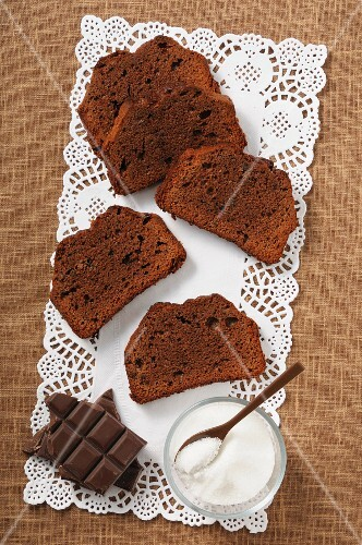 Slices of chocolate cake, sugar and pieces of chocolate on a doily