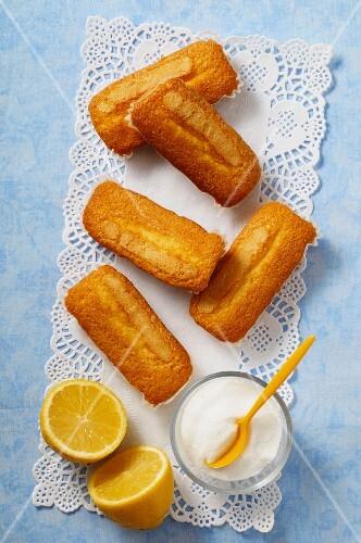 Mini lemon cakes, sugar and a lemon on a doily