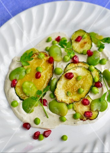 An appetiser of courgettes, peas, broad beans and pomegranate seeds