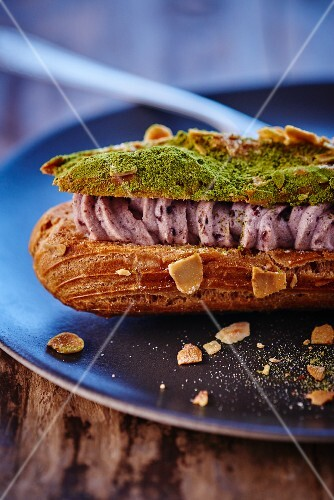 A eclair filled with cream, almonds and matcha tea powder