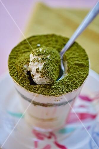 Matcha tea tiramisu in a glass with a spoon