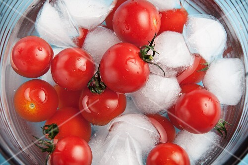 Cherry tomatoes in a bowl of ice water (seen from above)