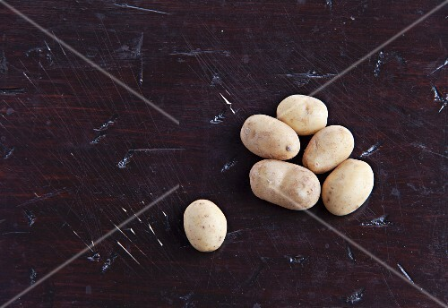 Fresh potatoes on a wooden surface