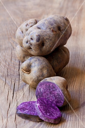 Purple potatoes, whole and halved, on a wooden surface