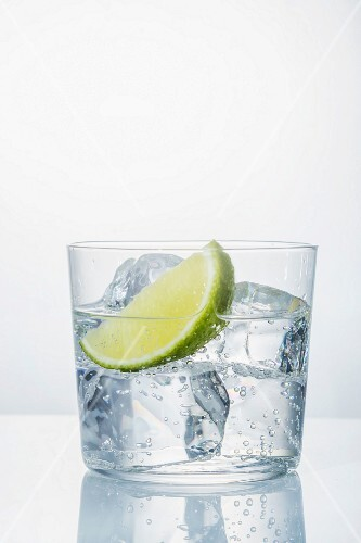 A glass of water with ice cubes and a lime wedge