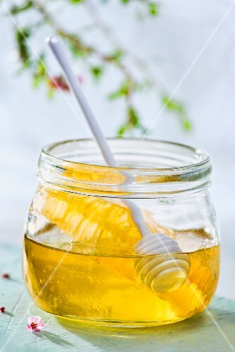 A jar of honey with honeycomb and a honey spoon