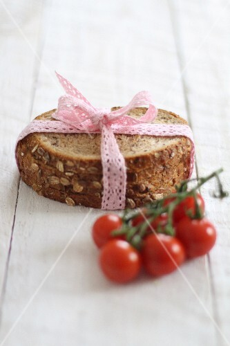 Slices of bread ties with a lace ribbon next to cherry tomatoes