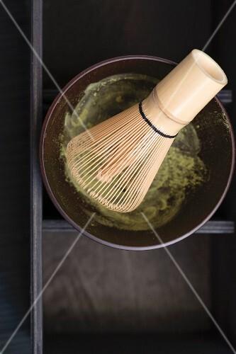 A matcha tea whisk in a matcha tea bowl with matcha tea powder
