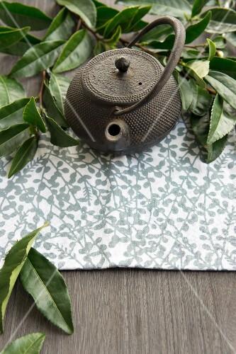 A teapot and fresh tea leaves