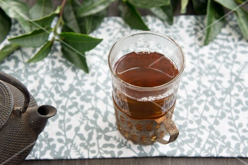 A glass of black tea, a teapot and fresh tea leaves