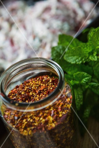 A jar of dried chilli seeds with fresh mint next to it