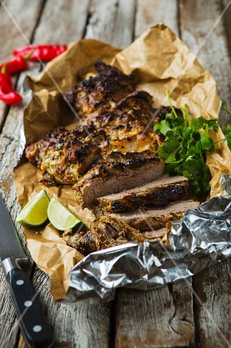 Roasted, sliced leg of lamb with coriander, chilli and lime on a wooden table