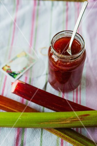 A jar of strawberry and rhubarb jam with fresh rhubarb, labels and utensils