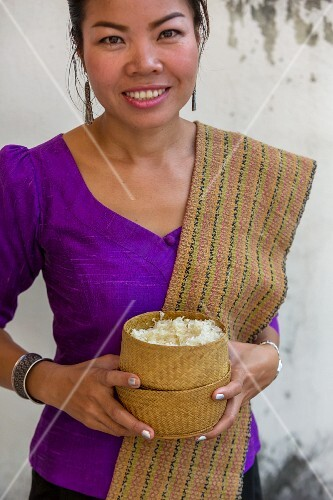 A woman holding baskets of sticky rice (Vientiane, Laos)