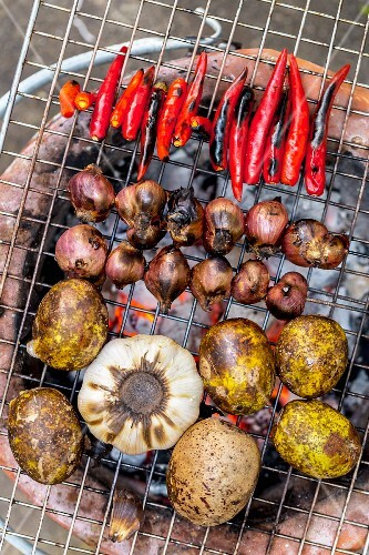 Shallots, garlic and ambarella fruits on a grill (Vientiane, Laos)