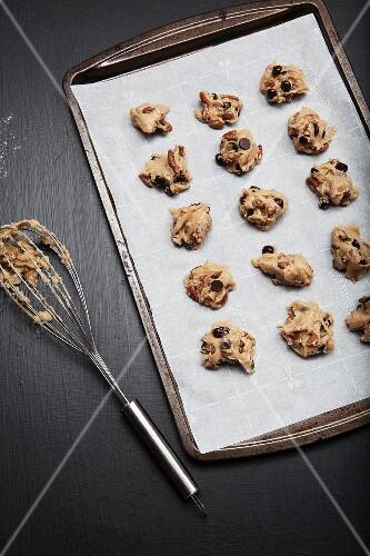 Unbaked chocolate chip and pecan nut cookies on a baking tray