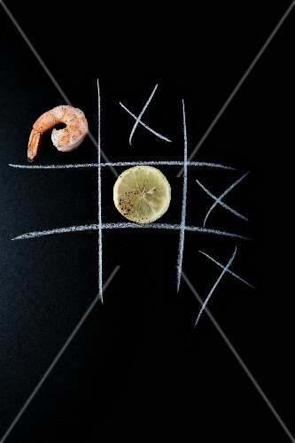 A prawn and a lemon slice on a chalkboard