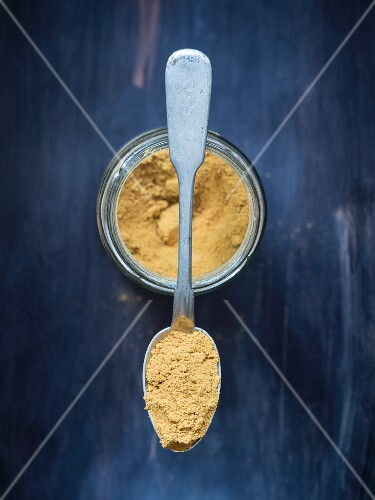 Ground turmeric on a silver spoon